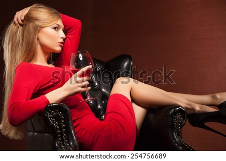 Closeup portrait of beautiful blonde lying in big black leather arm-chair with wine glass. - stock photo