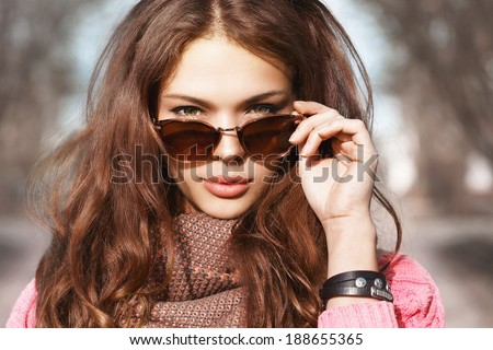 Closeup portrait of beautiful brunette girl standing on the street. Holding sunglasses with her hand and posing. Looking at camera. Urban city scene. Warm sunny weather. Outdoors - stock photo