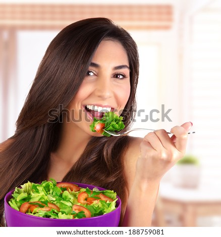 Closeup portrait of beautiful brunette woman eating salad at home on the kitchen, organic food, healthy lifestyle, dieting concept - stock photo