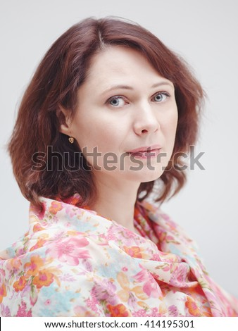 Closeup portrait of beautiful calm middle aged white caucasian brunette woman with green eyes covered with silk cotton scarf on her neck shoulders looking in camera on light white background - stock photo