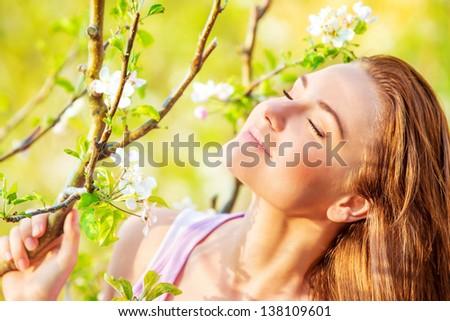Closeup portrait of beautiful calm woman enjoying spring nature with closed eyes, having fun outdoors, pleasure concept - stock photo