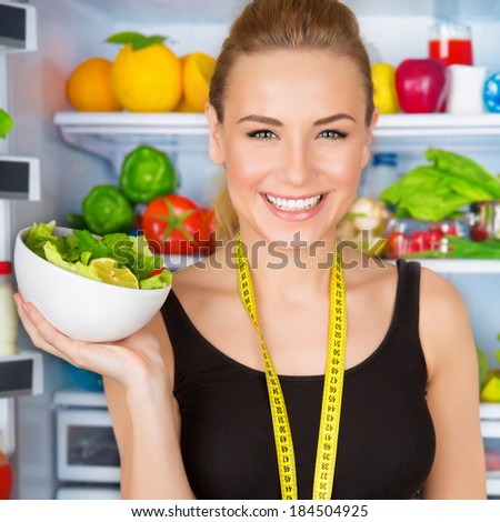 Closeup portrait of beautiful cheerful girl holding in hand bowl with fresh tasty green salad, dietitian recommending eating vegetables, healthy organic nutrition concept - stock photo