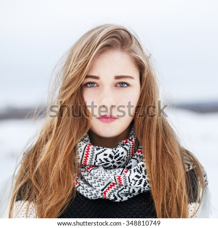 closeup portrait of beautiful cute serious young blond girl with bright long hair with pink lipstick with jacket and scarf on natural light background in field. Winter outdoor photo on cloudy weather - stock photo