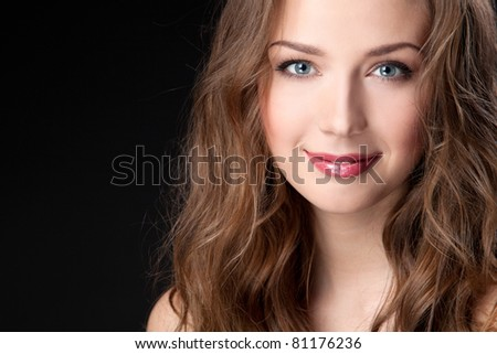 Closeup portrait of beautiful female fashion model on black background - stock photo