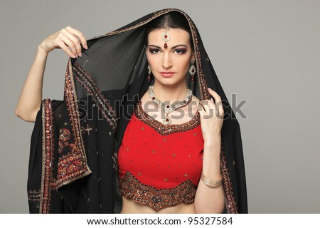 Closeup portrait of beautiful female posing in traditional indian costume with the scarf over her head - stock photo