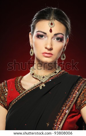 Closeup portrait of beautiful female wearing traditional indian costume over dark background - stock photo