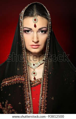 Closeup portrait of beautiful female wearing traditional indian costume with the scarf over her head - stock photo