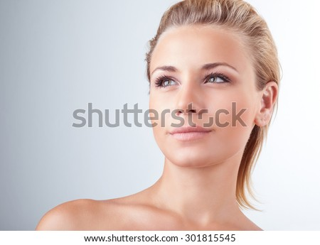 Closeup portrait of beautiful gentle blond woman with natural makeup over light background, face skin treatment, enjoying day spa