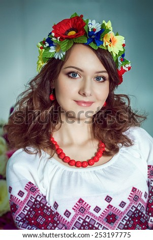 Closeup portrait of beautiful girl with red necklace and flowers wreath . Red earrings .Ukrainian national clothes.  - stock photo
