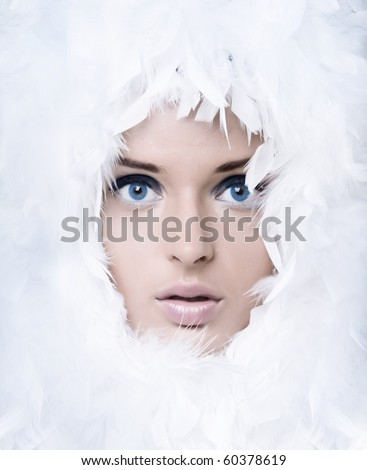 Closeup portrait of beautiful girl with white feathers - stock photo