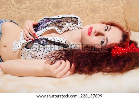 closeup portrait of beautiful gorgeous young redhead lady having fun relaxing lying on bed and sensually looking at camera on a light copy space background - stock photo