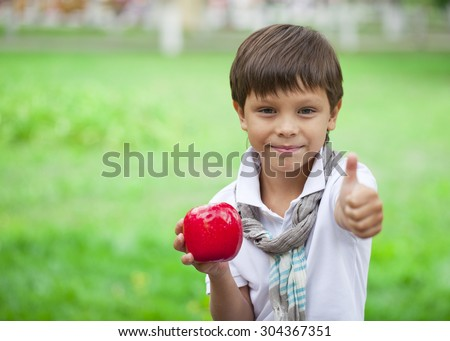 Closeup portrait of beautiful little boy holds red apple on the background of summer park - stock photo