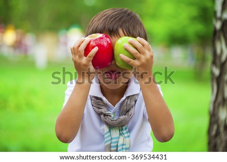 Closeup portrait of beautiful little boy holds two apples on the background of summer park - stock photo
