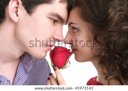 Closeup portrait of beautiful sexual couple with red rose isolated over white background - stock photo