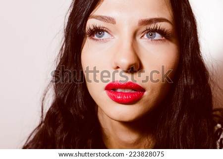 closeup portrait of beautiful sexy young lady with blue eyes and red lipstick having fun sensually looking at camera on light copy space background - stock photo