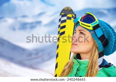 Closeup portrait of beautiful skier girl wearing mask and holding ski, enjoying winter holidays in Europe - stock photo