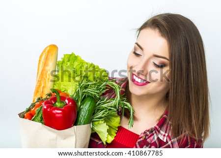 Closeup portrait of beautiful smiling woman holding shopping paper bag with organic fresh food, isolated over white background