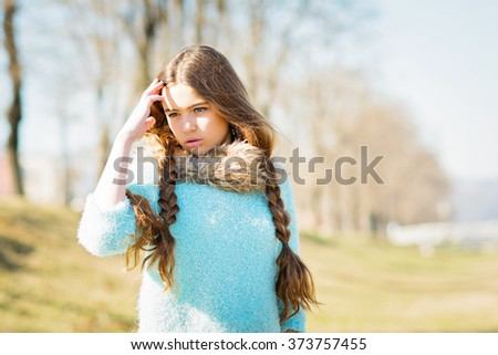 Closeup portrait of beautiful teenage girl with long braided hair, wearing fluffy mint green sweater, beige fur scarf. Young woman with luscious hair, natural light, back light, filter applied - stock photo