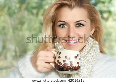 Closeup portrait of beautiful woman drink coffee outdoors.