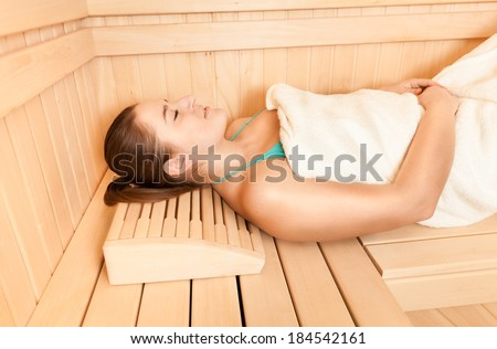 Closeup portrait of beautiful woman lying with closed eyes at steam bath