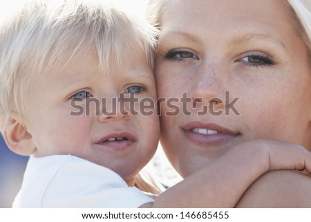 Closeup portrait of beautiful woman with baby boy cheek to cheek - stock photo