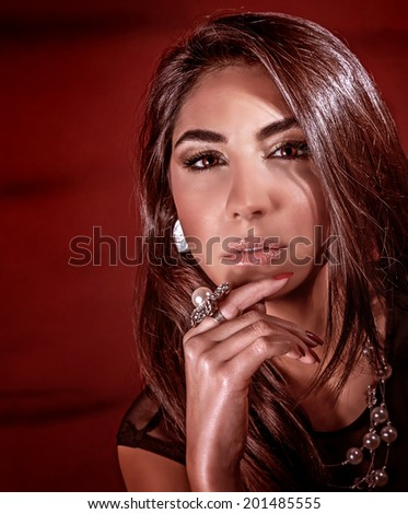 Closeup portrait of beautiful woman with perfect natural make-up isolated on dark red background, wearing luxury pearl jewellery, fashion style concept - stock photo