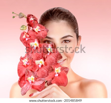 Closeup portrait of beautiful woman with red orchid flowers isolated on pink background, enjoying day spa, beauty treatment concept - stock photo