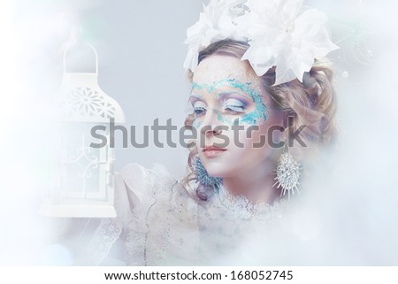 Closeup portrait of beautiful woman with winter style makeup and lantern in hand - stock photo
