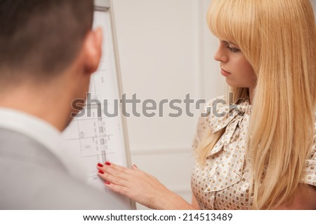 Closeup portrait of  beautiful young business lady architect discussing the architectural plan with her colleague engineer standing from behind, concept of teamwork, working process - stock photo