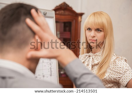 Closeup portrait of beautiful young business lady architect discussing the architectural plan with her colleague engineer standing from behind with his hands on head, conflict concept - stock photo