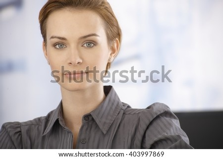 Closeup portrait of beautiful young businesswoman looking at camera. - stock photo