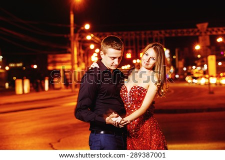 Closeup portrait of beautiful young couple embracing at night city street at colorful lights background.
