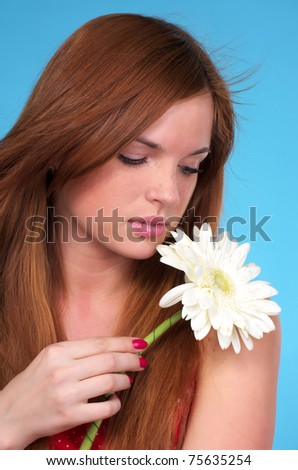 Closeup portrait of beautiful young female with white flower - stock photo