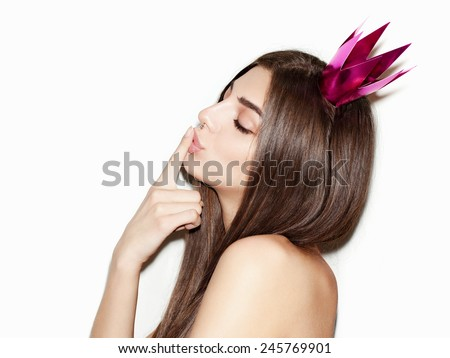 Closeup portrait of beautiful young girl with festive paper crown on her head. Fresh clean skin, natural makeup. Closing eyes and finger next to her pink lips. White background, not isolated. Inside - stock photo