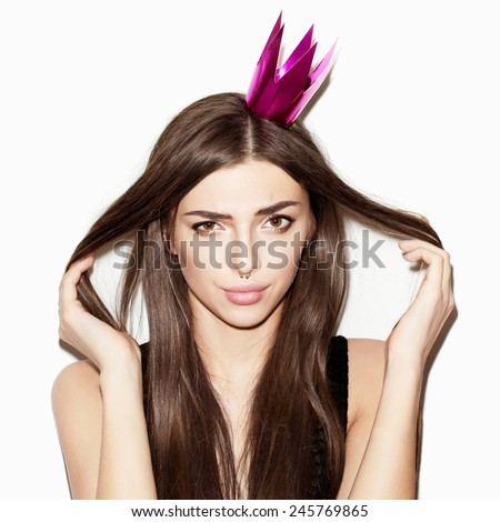 Closeup portrait of beautiful young girl with paper festive crown on her head. Fresh clean skin, natural makeup and pink lips. Brown eyes and long hair. White background, not isolated - stock photo