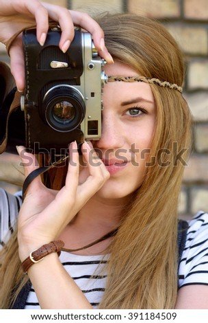 closeup portrait of beautiful young girl with retro camera, outdoors shoot - stock photo