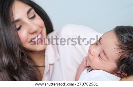 Closeup portrait of beautiful young happy mother having fun with her little newborn baby at home, enjoying first day of motherhood, love and happiness concept - stock photo