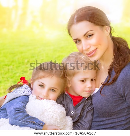 Closeup portrait of beautiful young mother with cute daughter and son sitting on the meadow, bright sun light, summer vacation, love and togetherness concept - stock photo