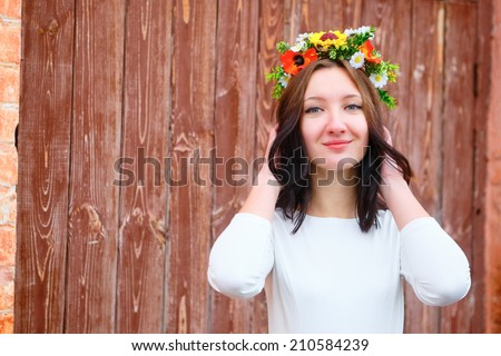 Closeup portrait of beautiful young smile woman with flower wreath on her head near the wooden door. Beauty concept - stock photo