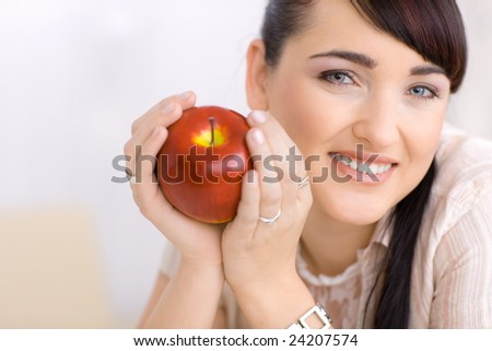 Closeup portrait of beautiful young woman holding red apple in hands, smiling happily.