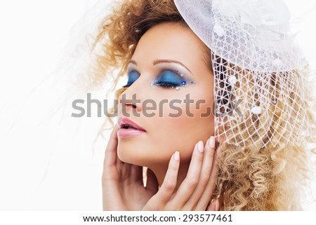 Closeup portrait of beautiful young woman in wedding hat with bright blue makeup. Isolated over white background. Copy space. - stock photo
