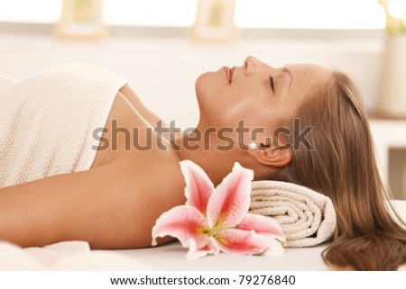 Closeup portrait of beautiful young woman lying on massage bed at spa, smiling.? - stock photo