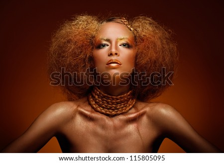 closeup portrait of beautiful young woman with creative makeup and hairstyle against brown background - stock photo