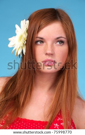 Closeup portrait of beautiful young woman with flower in hair - stock photo