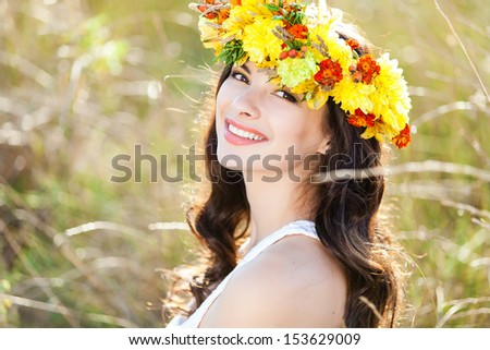 Closeup portrait of beautiful young woman with flower wreath on her head against field