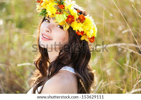Closeup portrait of beautiful young woman with flower wreath on her head against summer field