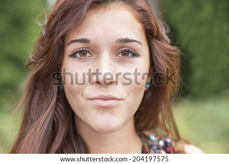 Closeup portrait of beautiful young woman with freckles. - stock photo