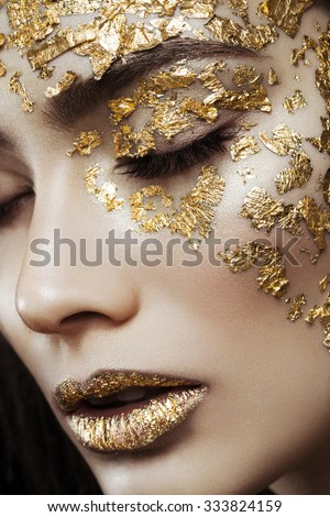 Closeup portrait of beautiful young woman with golden foil on face and lips. Creative makeup. Long hair - stock photo