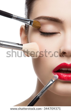 Closeup portrait of beautiful young woman with makeup brushes. Red lips. Isolated over white background. - stock photo