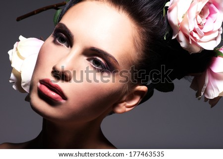 Closeup portrait of beautiful young woman with pink flowers in hair - on a gray background.